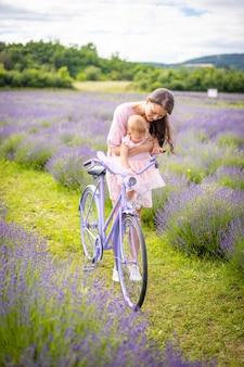 Mutter mit ihrer kleinen tochter auf lila fahrrad auf lavendelhintergrund tschechien