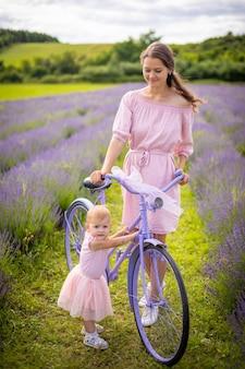 Mutter mit ihrer kleinen tochter auf lila fahrrad auf lavendelhintergrund tschechienlav