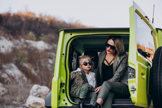 Mutter mit ihrer kleinen tochter, die hinten im auto sitzt