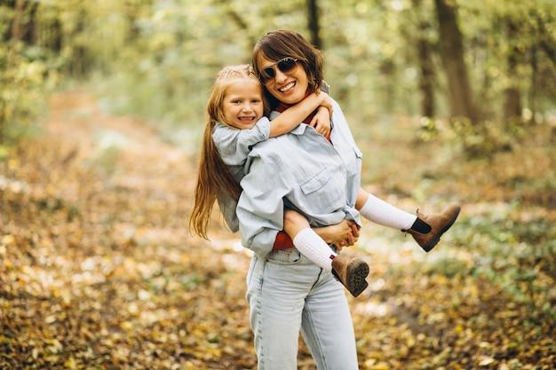Mutter mit ihrer kleinen tochter im wald voller goldener blätter