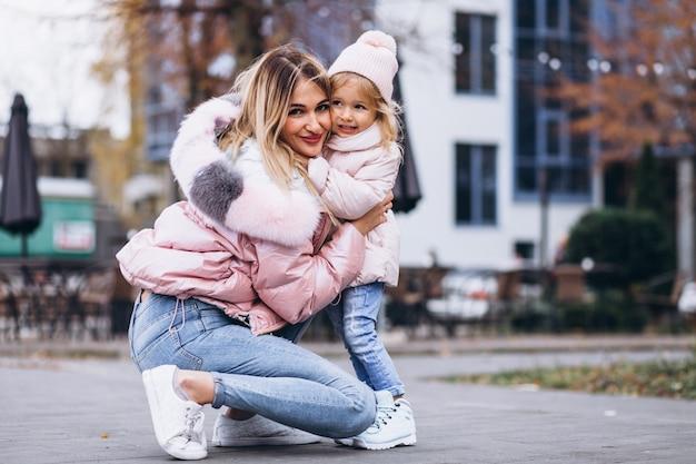 Mutter mit ihrer kleinen tochter in warmem tuch am straßenrand