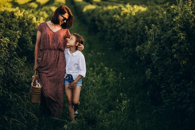 Mutter mit ihrer tochter, die in einem grünen feld geht
