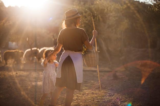 Mutter mit ihrer tochter, die korb und stock im bauernhof hält