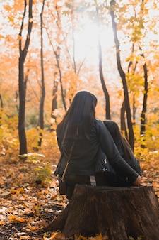 Mutter mit ihrer tochter sitzt auf einem baumstumpf im herbstpark alleinerziehende und saisonkonzept