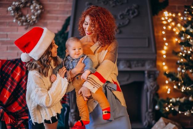 Mutter mit ihrer tochter und ihrem sohn zu weihnachten am weihnachtsbaum