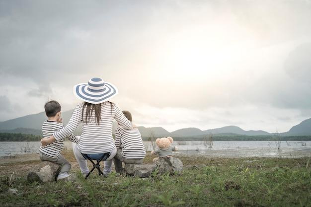 Mutter mit jungen töchtern und sohn auf picknick nahe dem see.