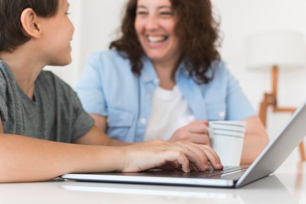 Mutter mit kind arbeitet am laptop