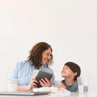 Mutter mit kind, das an tablette arbeitet