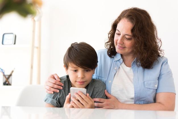 Mutter mit kind, das auf smartphone schaut