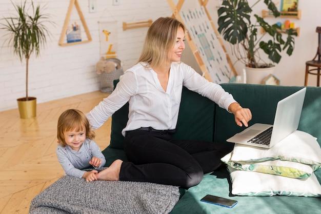 Mutter mit kind, das zu hause arbeitet