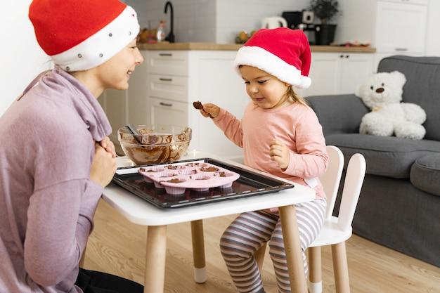 Mutter mit kind, das zu hause feiertagsplätzchen vorbereitet. glückliche familienzeit zusammen. hochwertiges foto
