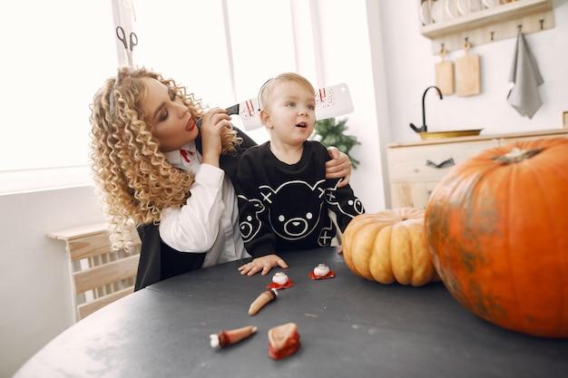 Mutter mit kind in kostümen und make-up. familie bereiten sich auf die feier von halloween vor.