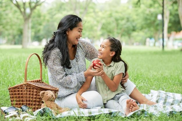 Mutter mit kind sitzt auf einem picknick