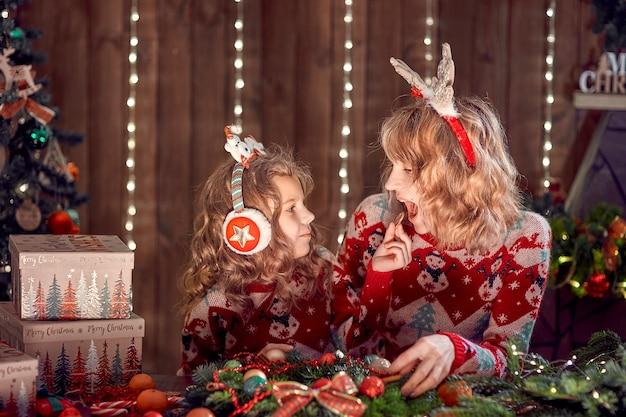Mutter mit kindermädchen nahe weihnachtsbaum
