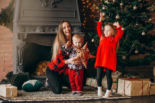 Mutter mit kindern am weihnachtsbaum