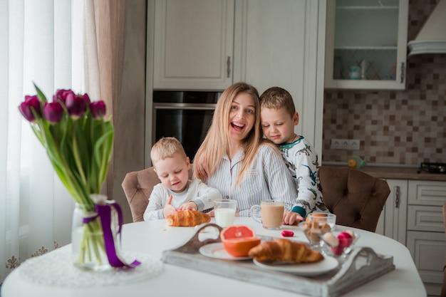 Mutter mit kindern beim frühstück in der küche
