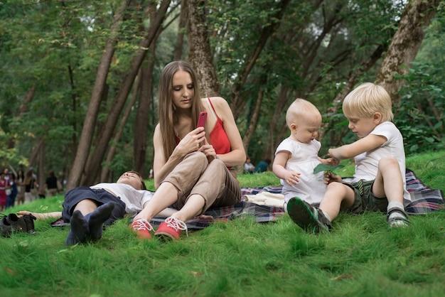 Mutter mit kindern beim picknick. mutter fotografiert kinder, wenn sie spielen