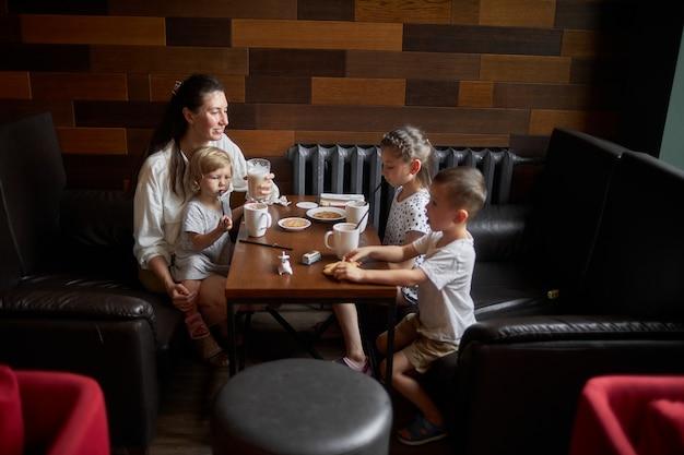 Mutter mit kindern, die heiße schokolade und latte in einem lokalen café trinken. sie lächeln und haben spaß. mutterschaftskonzept