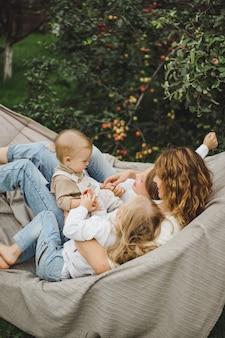 Mutter mit kindern, die spaß in einer hängematte haben. mutter und kinder in einer hängematte.