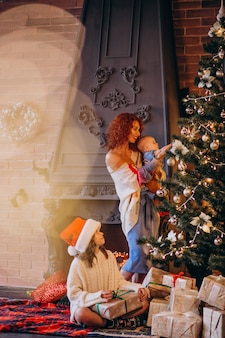 Mutter mit kindern, die weihnachtsbaum verzieren