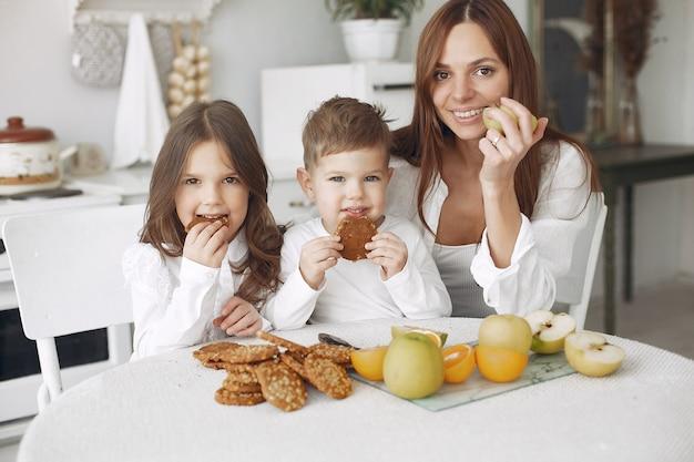 Mutter mit kindern sitzen in einer küche und essen