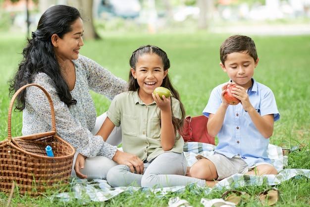Mutter mit kindern sitzt auf einem picknick