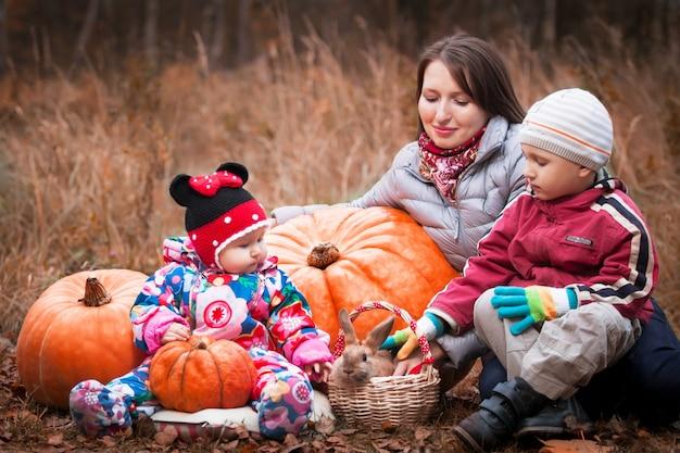 Mutter mit kindern sitzt neben dem kürbis und streichelt den hasen im korb