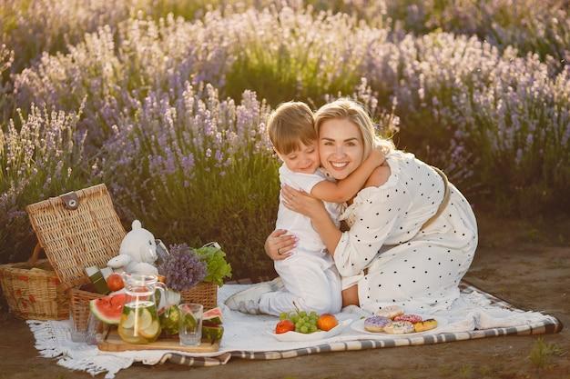 Mutter mit kleinem sohn auf lavendelfeld. frau auf einem picknick mit sohn.