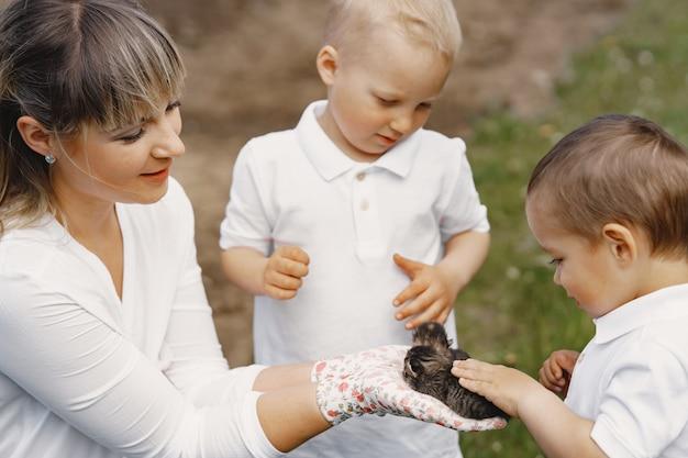 Mutter mit kleinem sohn, der in einem sommerhof spielt