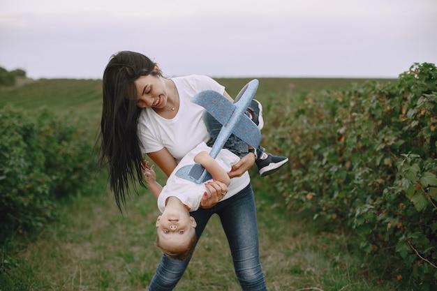 Mutter mit kleinem sohn, der mit spielzeugflugzeug spielt