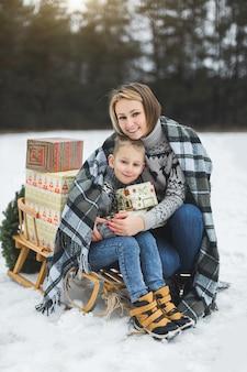 Mutter mit kleinem sohn im winterparkschlittenfahren. mutter und kind sitzen zusammen auf holzschlitten