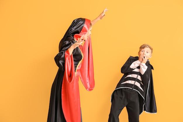 Mutter mit kleinem sohn in den halloween-kostümen auf farbe