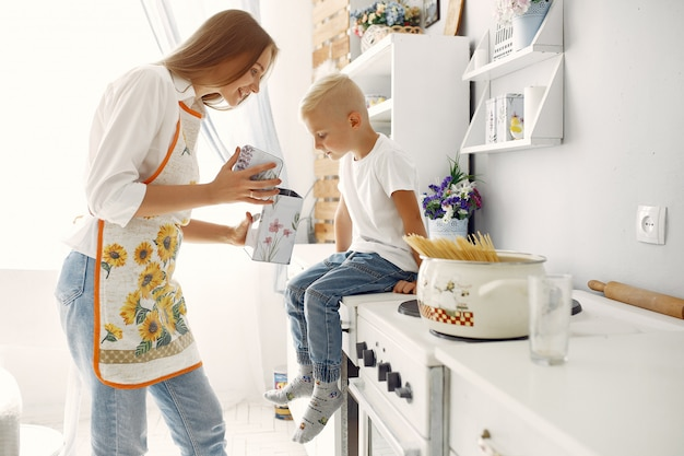 Mutter mit kleinen kindern, die zu hause kochen