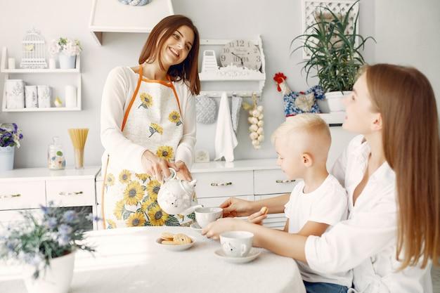 Mutter mit kleinen kindern, die zu hause tee trinken