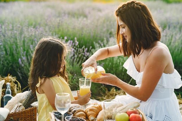 Mutter mit kleiner tochter auf lavendelfeld. schöne frau und niedliches baby, das im wiesenfeld spielt. familie bei einem picknick.