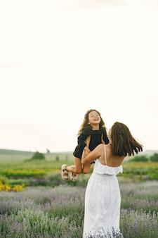 Mutter mit kleiner tochter auf lavendelfeld. schöne frau und niedliches baby, das im wiesenfeld spielt. familienurlaub im sommertag.