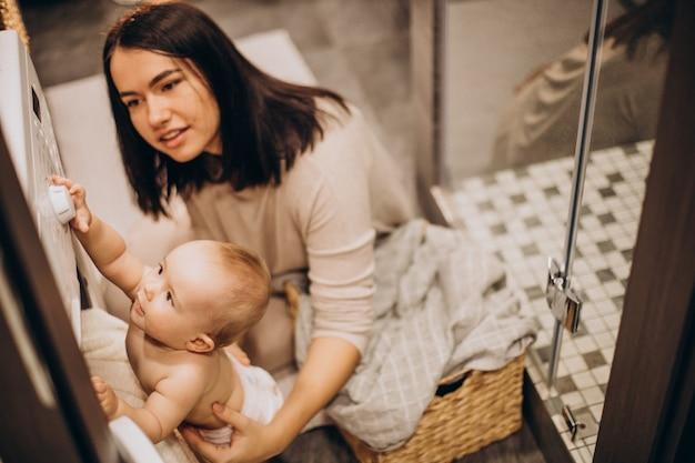 Mutter mit kleiner tochter, die wäsche zu hause macht