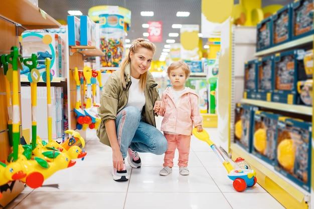 Mutter mit kleiner tochter im kinderladen. mutter und kind wählen zusammen spielzeug im supermarkt