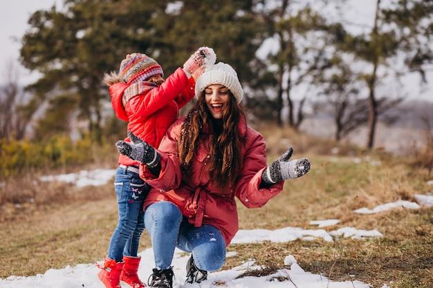 Mutter mit kleiner tochter in einem winterwald