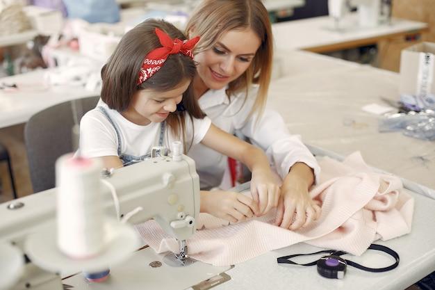 Mutter mit kleiner tochter nähen kleidung in der fabrik