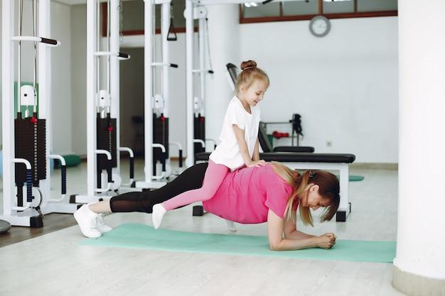 Mutter mit kleiner tochter nehmen an gymnastik in der turnhalle teil
