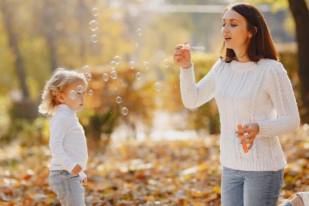 Mutter mit kleiner tochter spielt mit einer blase