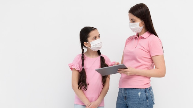 Mutter mit maske, die tablette hält
