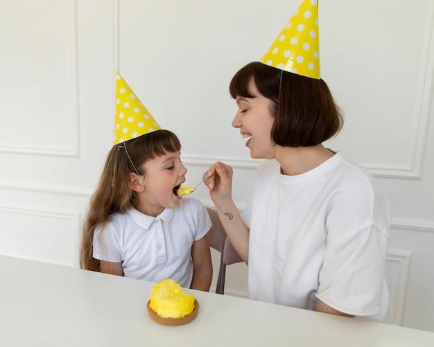Mutter mit mittlerem schuss, die mädchen-cupcake gibt