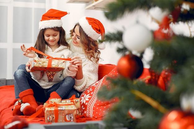 Mutter mit netter tochter in weihnachtsdekorationen