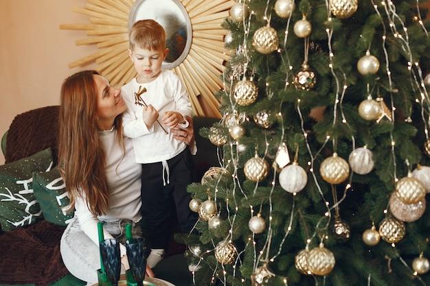 Mutter mit niedlichem sohn nahe weihnachtsbaum