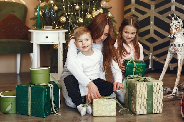 Mutter mit niedlichen kindern nahe weihnachtsbaum