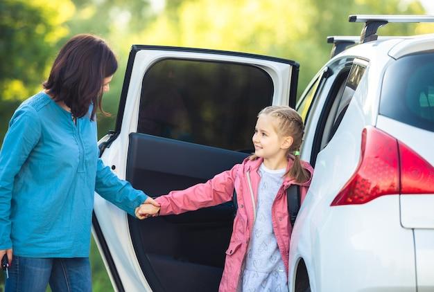 Mutter mit schulmädchen, das nach dem unterricht im auto sitzt