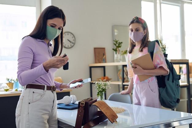 Mutter mit smartphone, die autoschlüssel prüft, während sie mit jugendlicher tochter in der maske fertig ist, um während des coronavirus zu unterrichten