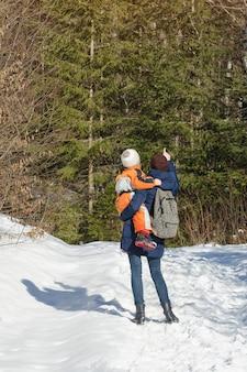 Mutter mit sohn in armen und rucksack steht